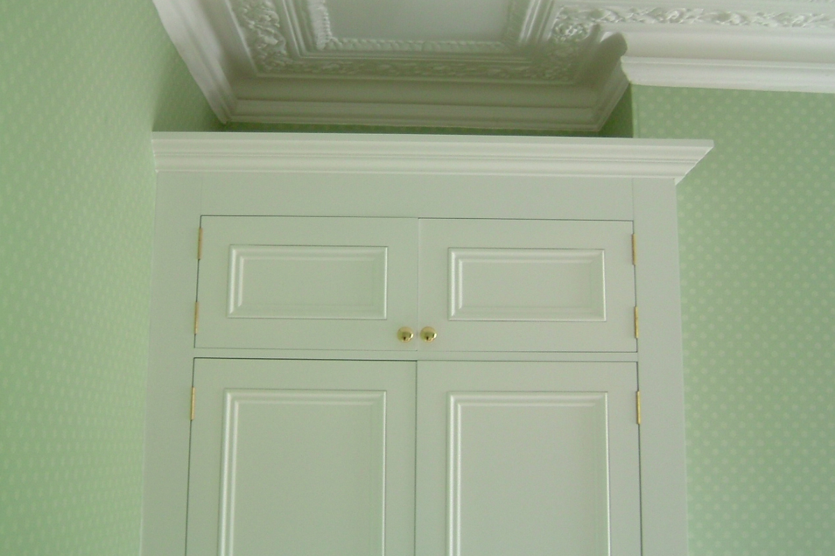 white panelled wardrobe doors with storage space above