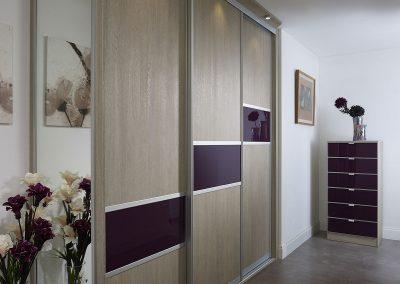 Wardrobe - contemporary sliding doors - wood effect finish - purple glass panels