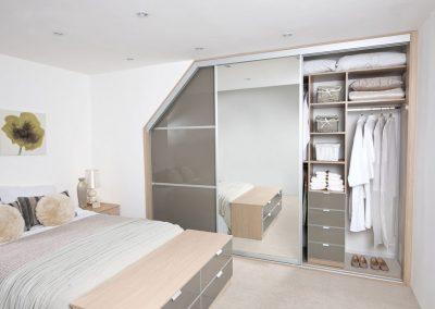 Wardrobe - angled contemporary sliding doors - grey glass - dressing mirror - matching interior drawers.